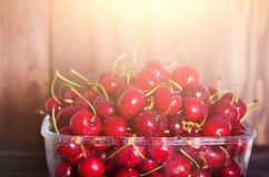 Sweet red cherries in glass bowl on dark wooden backgound with copy space. Sunny summer and harvest concept. Sunlight. Effect. Vegan, vegetarian, raw food Stock Images