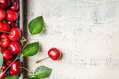 Sweet red cherries with leaves on white wooden vintage background, top view. Summer fruits Royalty Free Stock Photos