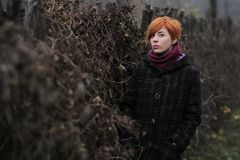 Sweet red-haired girl in a black coat and purple knitted scarf is standing by the fence overgrown with grapevine or ivy Royalty Free Stock Images
