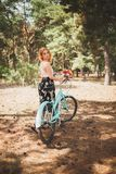 Young smiling girl standing next to a bicycle with a bouquet of flowers in the park The best time to walk with a bicycle. A sweet red-haired girl stands near her stock photography