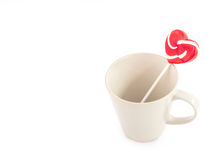 Sweet red heart lollipop on empty mug on white background, lover Royalty Free Stock Photos
