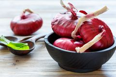 Sweet red onions in a black wooden bowl. Royalty Free Stock Image