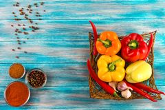 Fresh vegetables,.Sweet red, yellow, green, orange pepper in basket on wooden background.  Red pepper spice  and  black pepper. Sweet red, yellow, green, orange Royalty Free Stock Images