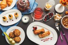 Restaurant breakfast with various sweet treats. Sweet restaurant breakfast with oatmeal cookies, croissants, yogurt, cheese pancakes, muesli, fresh berries and Stock Photos