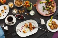 Restaurant breakfast with various sweet treats. Sweet restaurant breakfast with oatmeal cookies, croissants, yogurt, cheese pancakes, muesli, fresh berries and Royalty Free Stock Photos