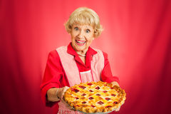 Granny Holding Lattice Top Cherry Pie. Sweet retro grandmother holding a freshly baked lattice top cherry pie. Red background with plenty of room for text stock photo