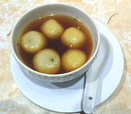 Sweet rice balls, Chinese Tang Yuan. Traditional favor of sesame fillings with sweet ginger soap stock image