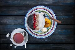 Sweet rice porridge with berries nuts and coconut chips with cutlery. Healthy breakfast or dessert. Bread with butter stock photo