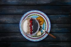 Sweet rice porridge with berries nuts and coconut chips, top view. Healthy breakfast or dessert. Bread with butter. Top. Sweet rice porridge with berries nuts Stock Image