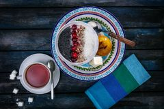 Sweet rice porridge with berries nuts and coconut chips, top view. Healthy breakfast or dessert. Tea and bread with. Butter on a colored wooden background Stock Photography