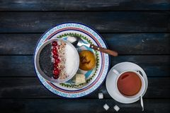 Sweet rice porridge with berries nuts and coconut chips, top view. Healthy breakfast or dessert. Tea and bread with. Butter on a colored wooden background Stock Images