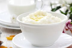 Sweet rice porridge with butter and mug of milk royalty free stock photos