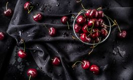 Sweet ripe cherries on dark tablecloth with water drops royalty free stock photos