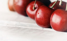 Sweet ripe cherries on white wooden table with water drops macro Royalty Free Stock Photography