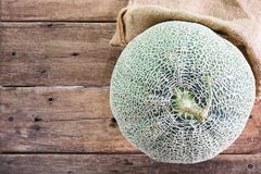 Sweet ripe green melon on brown wooden table texture background with gunny sack cloth Stock Photography