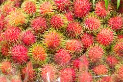 Sweet ripe rambutans with leaf on sale in supermarket. Sweet ripe rambutans, delicious rambutans, tropical fruit Stock Photo