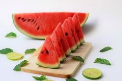 Sweet and ripe watermelon with limes and mint leaves in summertime royalty free stock photo