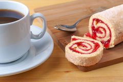 Sweet roll with jam and tea spoon on a cutting board. Cup of tea on a wooden table. Stock Photos