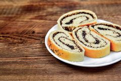 Sweet roll with poppy on plate and tea Royalty Free Stock Photo