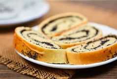 Sweet roll with poppy on plate and tea Royalty Free Stock Photos