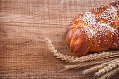 Sweet roll wheat ears on oak wooden board food and royalty free stock photo