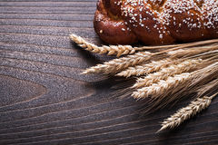 Sweet roll wheat rye ears on wooden background royalty free stock image