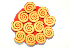 Sweet rolled cookies. Rolled yellow pastry served on red plate isolated over white background Royalty Free Stock Photo
