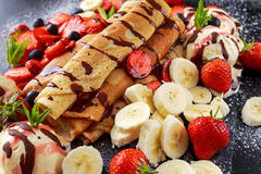 Sweet Rolled Pancakes with nutella, strawberry, blueberry, banana, ice cream. Royalty Free Stock Photo