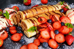 Sweet Rolled Pancakes with nutella, strawberry, blueberry and ice cream.  Stock Image