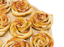 Sweet rolls with apples in the form of roses on wooden board on Royalty Free Stock Photography