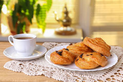 Sweet rolls with raisins and a cup of tea on the table Royalty Free Stock Photos