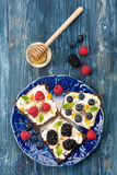 Sweet sandwich with berries, fruit, cream cheese, chia seeds and honey. Royalty Free Stock Photo