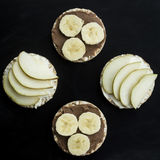 Sweet sandwiches with banana and peanut butter, cheese and pear on circular loaves buckwheat. top view Stock Photography