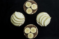 Sweet sandwiches with banana and peanut butter, cheese and pear on circular loaves buckwheat. top view. Round sandwiches - healthy snack for whole family royalty free stock photo
