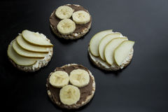 Sweet sandwiches with banana and peanut butter, cheese and pear on circular loaves buckwheat. top view Royalty Free Stock Photo