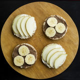 Sweet sandwiches with banana and peanut butter, cheese and pear on circular loaves buckwheat. top view. Round sandwiches - healthy snack for whole family royalty free stock image