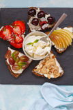 Sweet sandwiches with mascarpone. Cheese and berries, pear and peanut butter royalty free stock photos