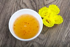 Sweet sauce. Yellow asian spicy sweet sauce on wood background Stock Image