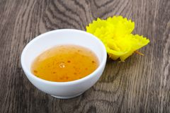Sweet sauce. Yellow asian spicy sweet sauce on wood background Royalty Free Stock Image
