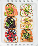 Sweet and savory breakfast toasts assortment. Sandwiches with fruit, vegetables, eggs, smoked salmon on white baking Royalty Free Stock Photography