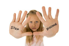 Sweet and scared little schoolgirl showing the text stop bullying written in her hands Royalty Free Stock Image