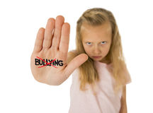 Sweet and scared little schoolgirl showing the word bullying scratched written in her hand Royalty Free Stock Photo
