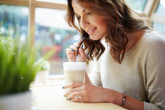 Sweet scent of coffee. Side close up portrait of young woman drinking ice coffee with straw Royalty Free Stock Images