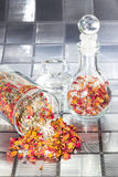 Sweet scented rose petal potpourri. In two glass containers on a tiled bathroom surface with one container on it side with the mixture of dried flowers and royalty free stock photo