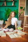 A sweet schoolgirl of junior classes with long blond hair with books, a school board and apples. School Fashion stock photo