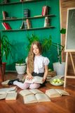 A sweet schoolgirl of junior classes with long blond hair with books, a school board and apples. School Fashion stock images