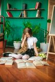 A sweet schoolgirl of junior classes with long blond hair with books, a school board and apples royalty free stock images