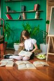 A sweet schoolgirl of junior classes with long blond hair with books, a school board and apples. School Fashion stock photos