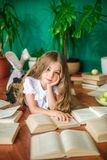 A sweet schoolgirl of junior classes with long blond hair with books, a school board and apples. School Fashion royalty free stock image