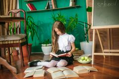 A sweet schoolgirl of junior classes with long blond hair with books, a school board and apples. School Fashion stock photography